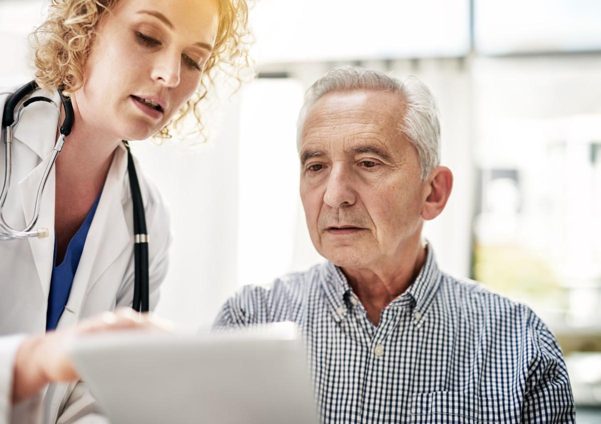 Lege forklarer en eldre mann informasjon på et nettbrett.