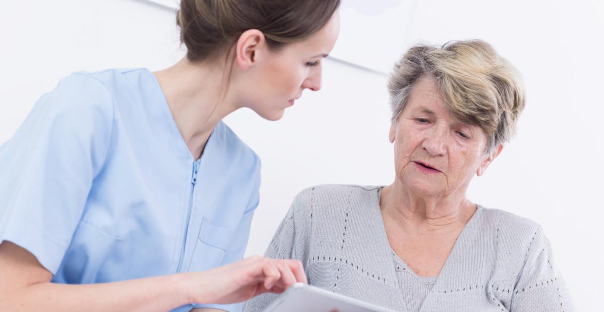 Helsearbeider som gir en eldre dame informasjon fra et nettbrett.