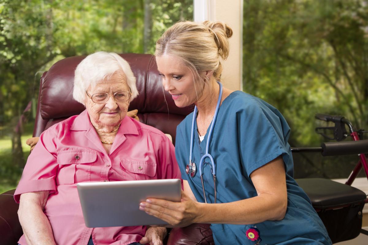Sykepleier som viser en eldre kvinne informasjon på et nettbrett