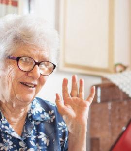Gledelig overrasket eldre dame som ser på en skjerm.