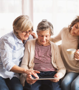 3 kvinner, mor. datter og barnebarn ser på et nettbrett i en sofa.